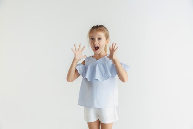 Stilvolles kleines lächelndes mädchen, das in der freizeitkleidung lokalisiert auf weißem raum aufwirft. kaukasisches blondes weibliches modell. menschliche gefühle, gesichtsausdruck, kindheit, verkauf