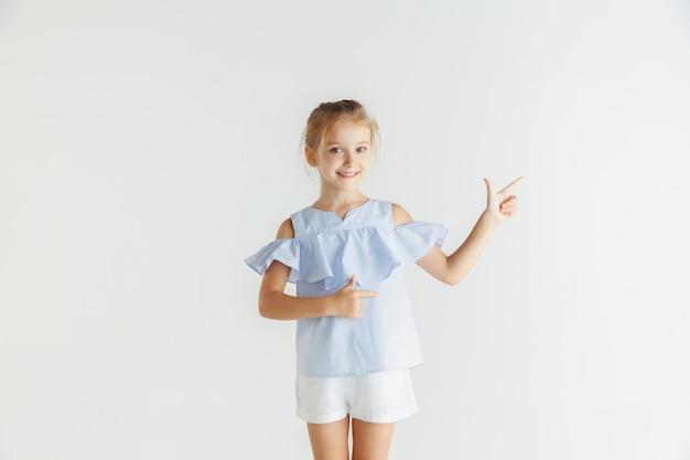 Stilvolles kleines lächelndes mädchen, das in der freizeitkleidung lokalisiert auf weißem studio aufwirft