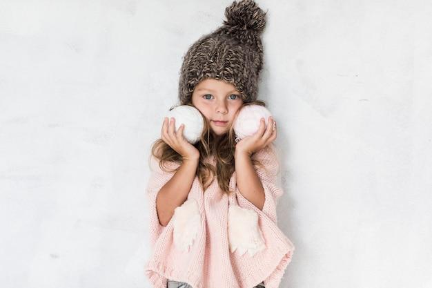 Stilvolles kleines mädchen, das schneebälle hält