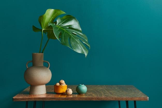 Stilvolles konzept der wohnzimmereinrichtung mit walnusstisch, tropischem blatt in vase, keramikgefäß und eleganten persönlichen accessoires in moderner vintage-wohnkultur. grüne wand. platz kopieren.