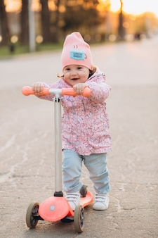 Stilvolles lächeln des kleinen mädchens und reitet einen roller im park bei sonnenuntergang