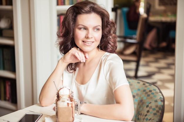 Stilvolles lächelndes mädchen im café retrostyle