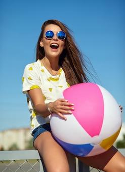 Stilvolles lächelndes schönes modell der jungen frau des lustigen verrückten zaubers in der zufälligen kleidung des hellen hippie-sommers, die in der straße hinter blauem himmel aufwirft und auf dem zaun sitzt. spielen mit buntem aufblasbarem b