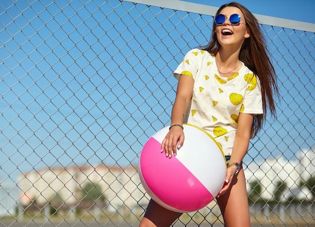 Stilvolles lächelndes schönes modell der jungen frau des lustigen verrückten zaubers in der zufälligen kleidung des hellen hippie-sommers, die in der straße hinter eisengitter und blauem himmel aufwirft. spielen mit buntem aufblasbarem ball floa