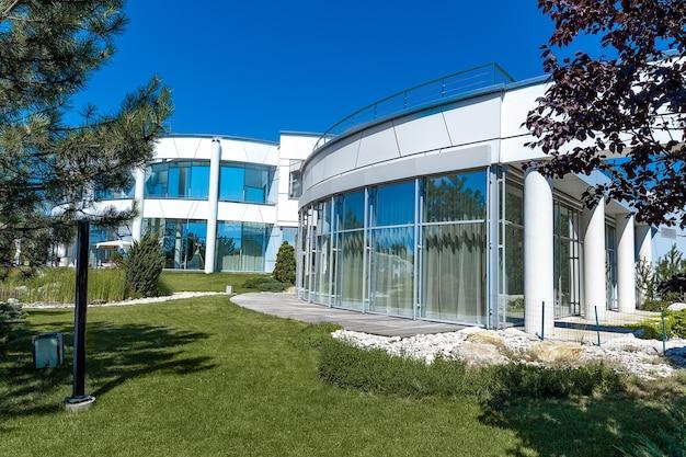 Stilvolles landhaus mit glaswänden und säulen umgeben von grünem rasen