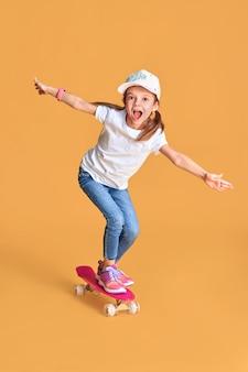 Stilvolles lustiges mädchen, das weißes t-shirt, blaue jeans und turnschuhe trägt, die auf skateboard über gelbem hintergrund stehen