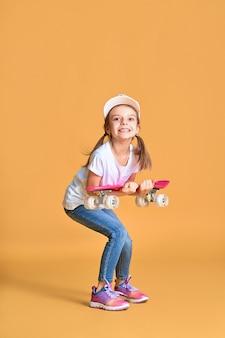 Stilvolles lustiges mädchen, das weißes t-shirt, blaue jeans und turnschuhe trägt und skateboard über gelber wand hält
