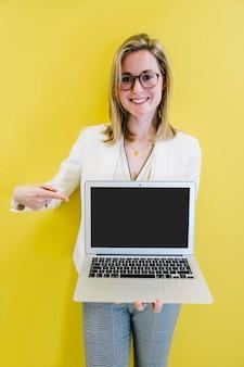Stilvolles mädchen, das auf bildschirm des laptops zeigt