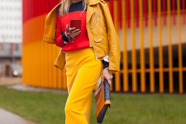 Stilvolles mädchen, das auf der straße in der hellen gelben kleidung steht