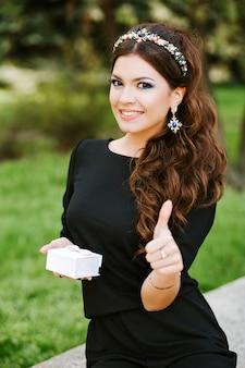 Stilvolles mädchen, das ein geschenk hält. tragen eines schwarzen kleides, teuren schmucks, ring, ohrringe, armband. den hintergrund verwischen, lächelnd, glücklich. daumen hoch.
