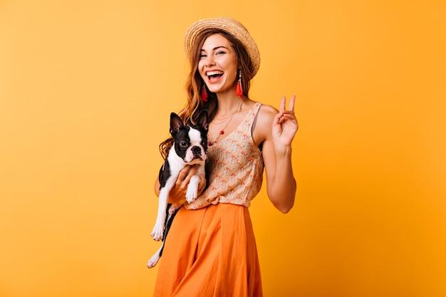 Stilvolles mädchen, das französische bulldogge hält und lacht. optimistische rothaarige dame, die sich mit ihrem hund im studio entspannt.
