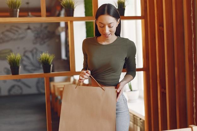 Stilvolles mädchen, das in einem café mit einkaufstaschen steht