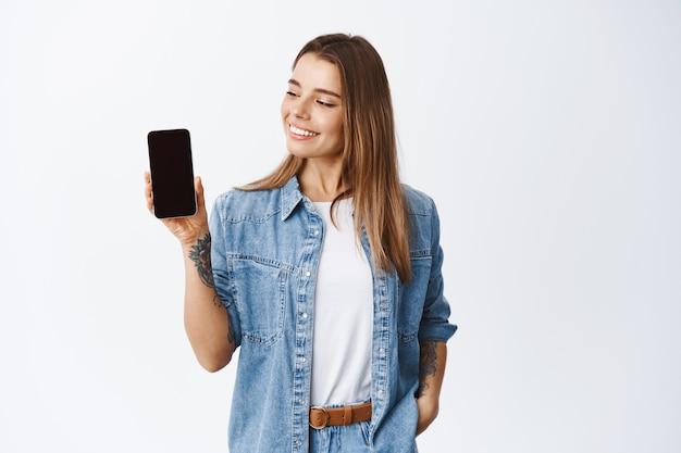 Stilvolles mädchen, das leeren handybildschirm zeigt und zufrieden aussieht, anwendung für smartphone empfiehlt, einkaufsseite demonstriert, weiße wand