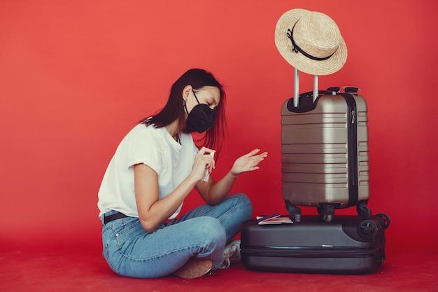 Stilvolles mädchen, das mit reiseausrüstung auf einer roten wand aufwirft
