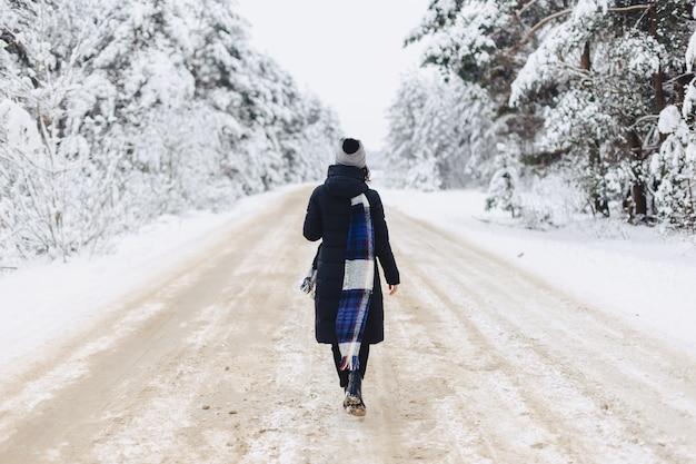 Stilvolles mädchen, das mitten in einer straße auf einem schneebedeckten wald geht