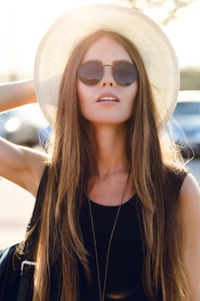 Stilvolles mädchen, das nahe straße steht und kurzes schwarzes kleid, strohhut, schwarze brille und schwarzen rucksack trägt. sie lächelt in den warmen strahlen der untergehenden sonne. sie berührt ihre sonnenbrille mit der hand
