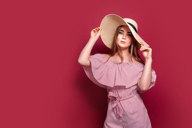Stilvolles mädchen im gestreiften kleid stehend im strohhut und in den großen runden gläsern auf rosa hintergrund
