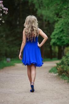 Stilvolles mädchen im hellblauen kleid und in den hochhackigen schuhen im park in der rückansicht des sonnigen tages. schöne blonde frau im kurzen kleid, das auf straße geht. sexy frau im kurzen blauen kleid im freien rückansicht