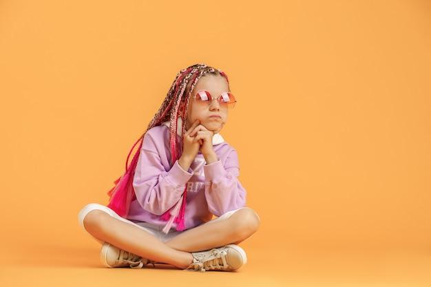 Stilvolles mädchen in abgerundeten gläsern mit rosa dreadlocks, die auf gelbem hintergrund aufwerfen