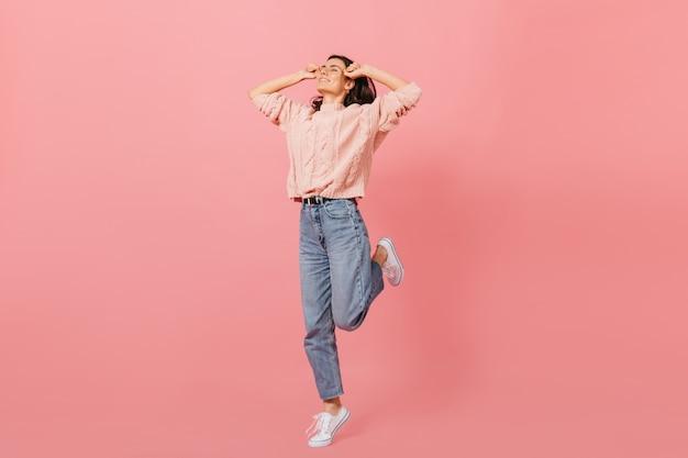 Stilvolles mädchen in der jeans der mutter und im warmen übergroßen pullover, der glücklich auf rosa hintergrund springt.