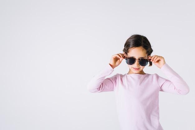 Stilvolles mädchen in der sonnenbrille, die kamera betrachtet