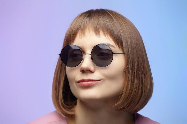 Stilvolles mädchen in der sonnenbrille. fotoshooting im studio auf einem rosa hintergrund