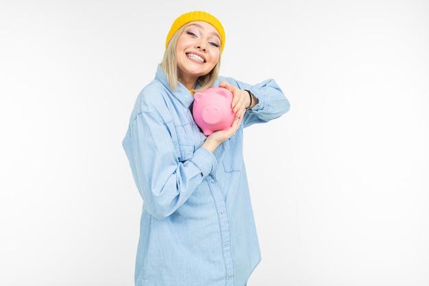 Stilvolles mädchen in einem blauen hemd mit einer bank für das sparen von finanzen auf einem weißen hintergrund mit kopienraum
