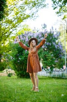 Stilvolles mädchen in einem braunen hut und einem hellen kleid auf einem hintergrund von lila üppigen büschen. junge frau mit einem lächeln im gesicht an einem sonnigen sommertag spaziert im park