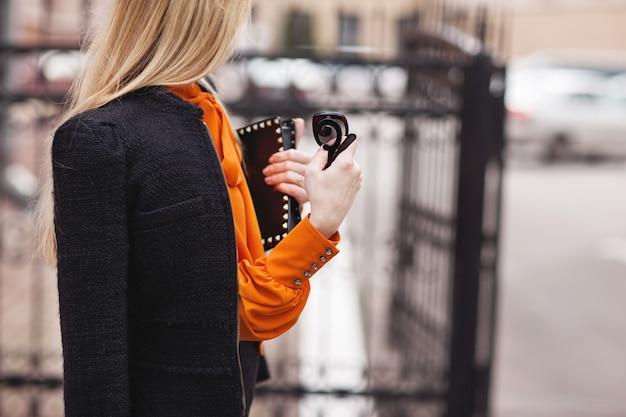 Stilvolles mädchen in einem schwarzen anzug und in einer orange bluse steht nahe dem zaun