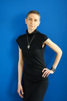 Stilvolles mädchen in einem schwarzen kleid, das auf einem blau aufwirft. kreatives modell arbeitet mit fotograf
