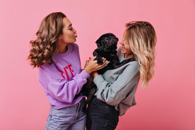 Stilvolles mädchen mit braunem glänzendem haar, das hund mit küssendem gesichtsausdruck betrachtet. innenporträt der fröhlichen blonden frau, die mit ihrem welpen auf rosig steht.
