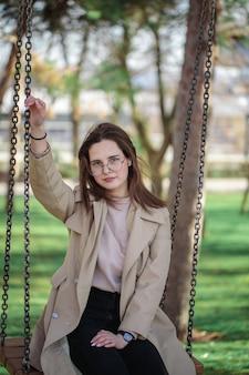 Stilvolles mädchen mit brille, draußen. teenager-mädchen auf einer schaukel, schönes porträt.