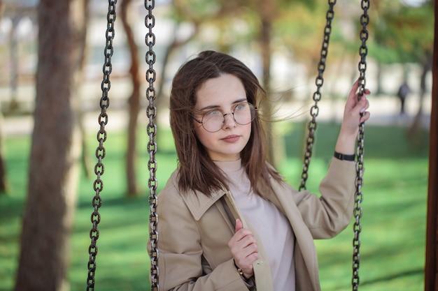 Stilvolles mädchen mit brille schaut weg, draußen. teenager-mädchen auf einer schaukel, schönes porträt.