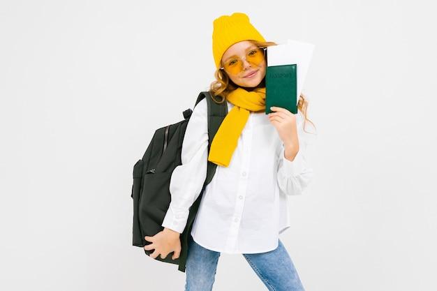 Stilvolles mädchen mit einem rucksack auf ihren schultern hält einen pass mit urlaubskarten auf einem weißen hintergrund mit kopienraum.