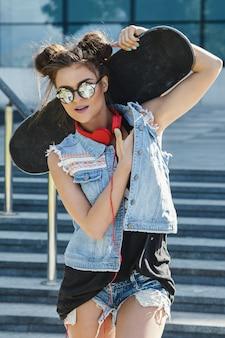 Stilvolles mädchen mit einem skateboard