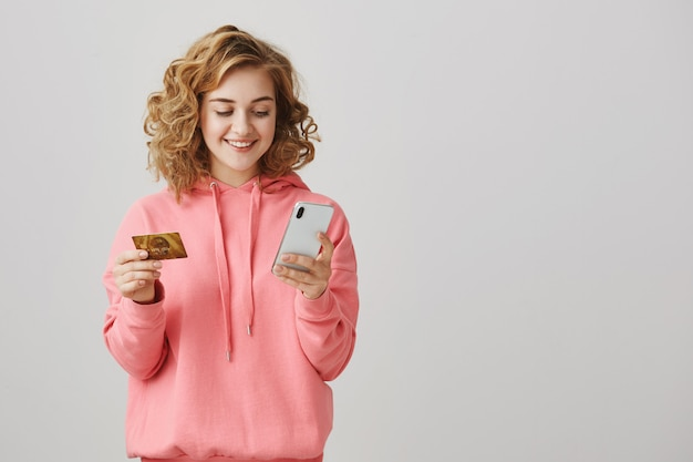 Stilvolles mädchen mit lockigen haaren, das online mit kreditkarte und smartphone einkauft