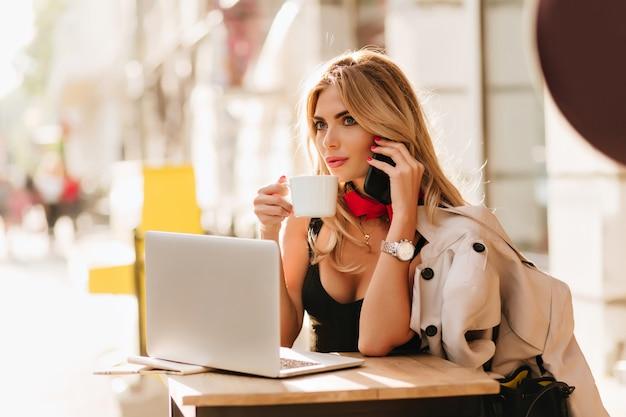 Stilvolles mädchen mit roter maniküre, die mit telefon und tasse kaffee auf unschärfehintergrund aufwirft