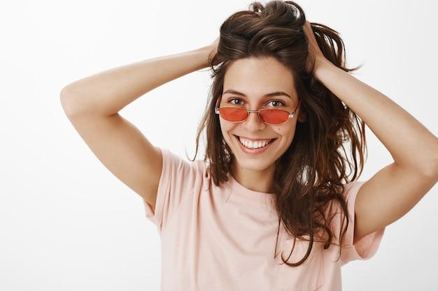 Stilvolles mädchen mit sonnenbrille, die gegen die weiße wand aufwirft