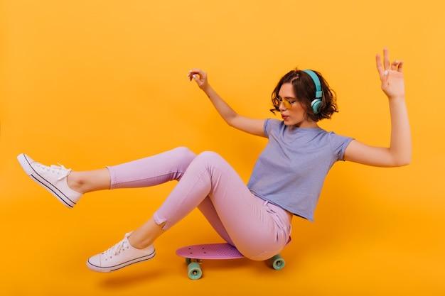 Stilvolles mädchen mit tätowierung, die auf longboard sitzt. angenehmes weibliches modell mit dem kurzen lockigen haar, das auf skateboard aufwirft und musik hört.