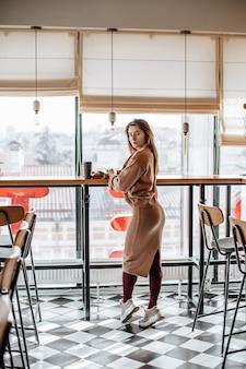 Stilvolles mädchen sitzt in einem café am tisch und trinkt kaffee. kaffee zum mitnehmen im pappbecher. frau mit roten haaren in einem beigen warmen anzug in gemütlicher atmosphäre. modernes interieur. ruhiger und angenehmer zeitvertreib.