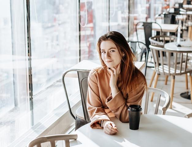 Stilvolles mädchen sitzt in einem café und trinkt kaffee. kaffee zum mitnehmen im pappbecher. frau mit ingwerhaar in einem beigen warmen anzug in gemütlicher atmosphäre. modernes interieur. ruhiger und angenehmer zeitvertreib