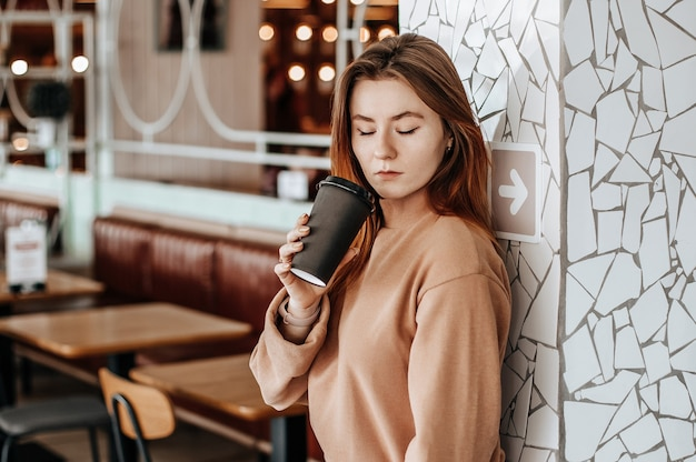 Stilvolles mädchen trinkt kaffee in einem café. eine frau mit roten haaren steht in einem beigen anzug an einer wand. modernes interieur. coffee to go im pappbecher