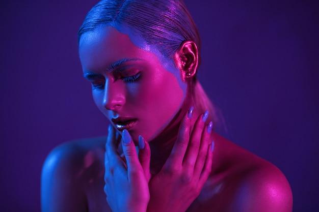 Stilvolles mädchenmodell im neonschatten mit gesenkten augen