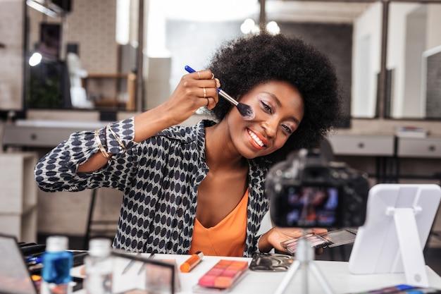 Stilvolles make-up. hübsche dunkelhäutige frau mit hellem make-up, die sich amüsiert fühlt, während sie rouge auf ihre wangen auftragt