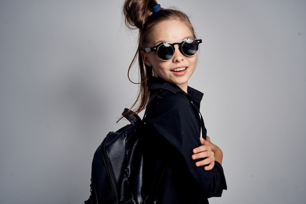 Stilvolles modebild eines kleinen mädchens in der schwarzen brille