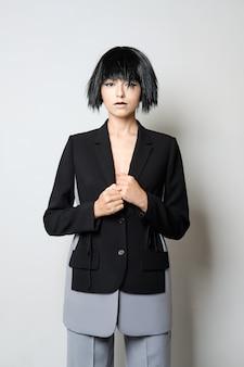 Stilvolles model in kurzer schwarzer perücke posiert im zweifarbigen hosenanzug mit weiter hose und jacke mit tiefem schnitt