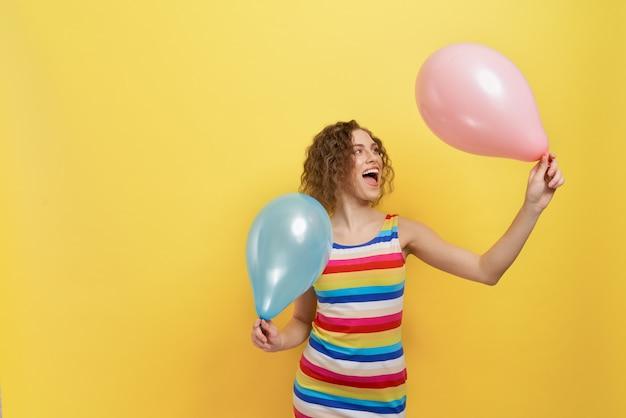 Stilvolles modell im gestreiften kleid mit zwei ballons.