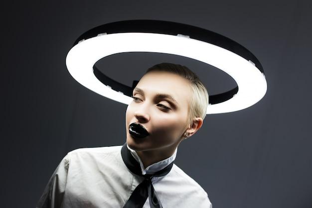 Stilvolles modeporträt einer blondine mit einem schwarzen lippenstift auf den lippen. der hintergrund ist eine lampe.