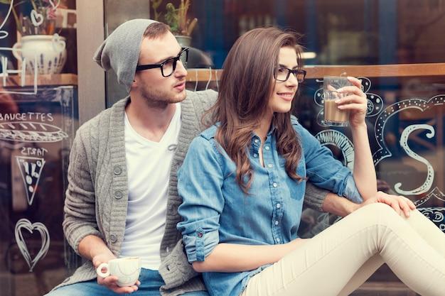 Stilvolles paar, das mit tasse kaffee außerhalb des cafés sitzt