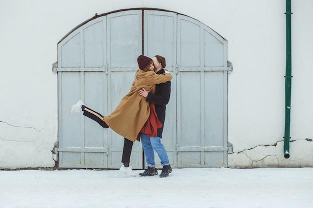 Stilvolles paar in klassischer winterkleidung, die nahes weißes historisches gebäude umarmt